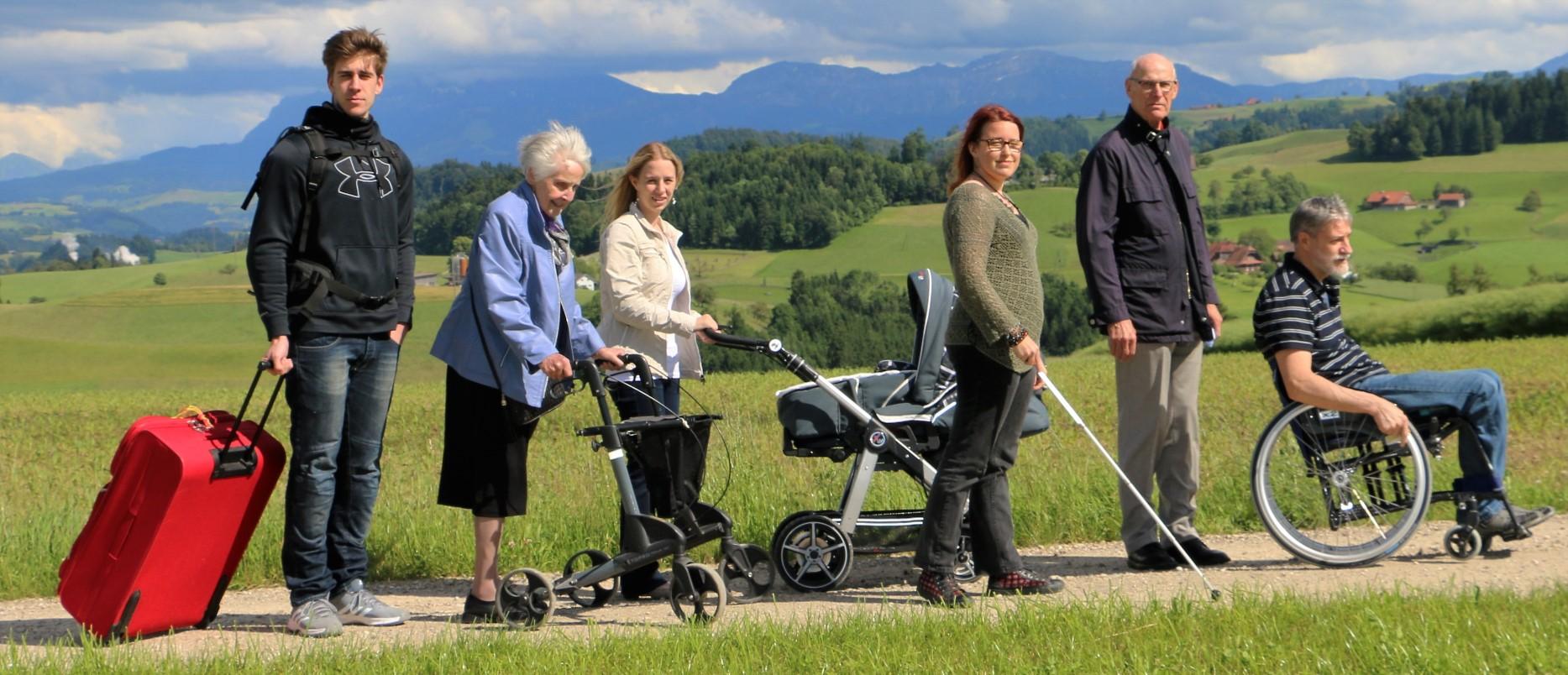 Sechs Personen auf einem Weg zwischen Wiesen, davon fünf mit Reisekoffer, Gehhilfe, Kinderwagen, Blindenstock oder Rollstuhl – Sie alle profitieren von einer hindernisfreien Bauweise.